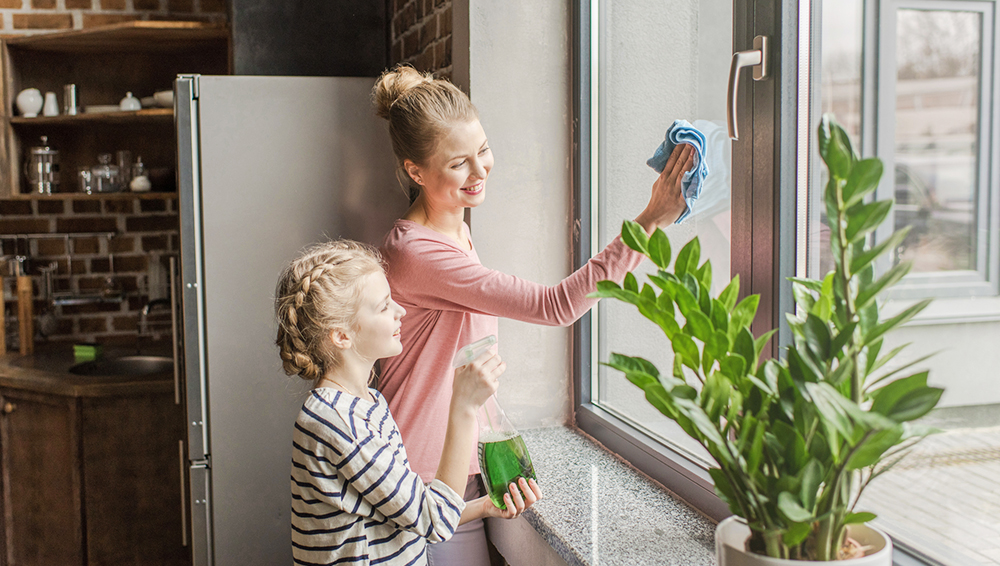 happy mother and daughter cleaning window with rag and spray bot